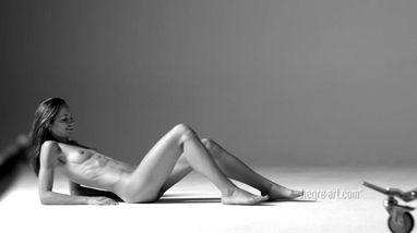 Худая модель занимается позированием в студии без лифчика и трусиков